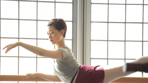 Girl in arabesque at the barre in front of a glass wall