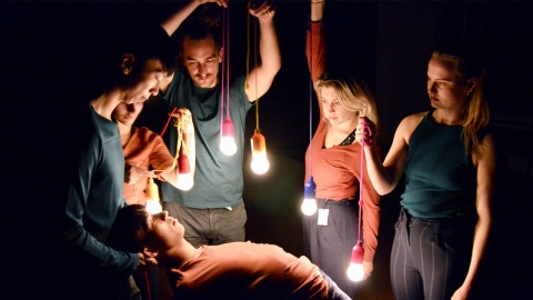 Five men and women stand in a circle, holding hanging lightbulbs over a man.