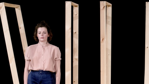 Photo of dance artist Elinor Lewis wearing a peach shirt and blue jeans standing in front of timber frames