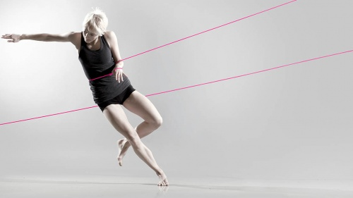 A full colour image showing one female dancer standing on one leg with her arm out to the side, her other arm is tied with a pink rope. Image by Stephen Berkeley-White