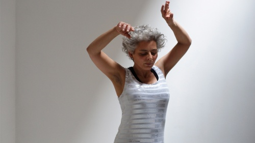 Wendy Houstoun - Pact With Pointlessness (the performer is standing in front of a white background wearing white, looking down with her arms up)