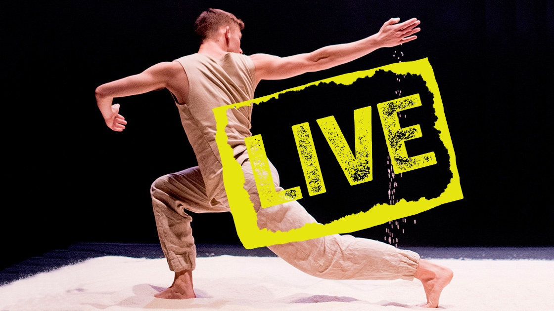 A full colour image showing a male dancer lunging with his arm outstretched and sand falling from his hand, image by Camilla Greenwell.