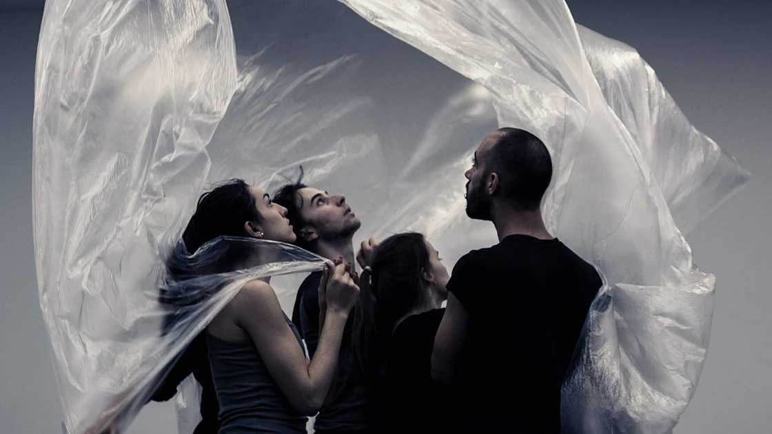 A full colour image showing a group of four dancers looking up towards a billowing sheet of plastic that's floating around them. Image by Despina Patsika