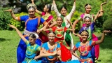 9 young people wearing South Asian dance outfits standing outside