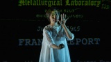 Dance artist Chisato Minamimura on stage in front of a projection featuring words