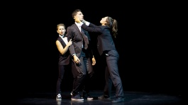 Dancers in suits teasing each other on stage