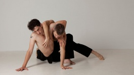 Two men are tangled in a complicated shape on the floor. They are on a beige backdrop.