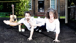 Anecdotal Evidence image. Two performers are in a plank position facing us looking at us gholding themselves up with one hand. The other arm is in the air facing the left hand side.