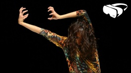 Performer holding arms over their head against a black background with a VR headset icon in the top right corner