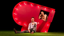 New Art Club Cupid's Revenge lead image: a performer is sat on the floor looking at us on grass with an arrow in his hand leaning against a large heart where another performer  with wings and topless is coming out of a window in the heart looking pensive
