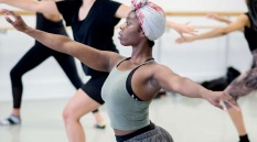 Woman wearing a grey vest and headwrap in a dance studio lunging with outstretched arms