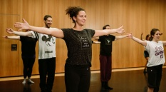 Photo of dance class participants in a dance studio holding arms outstretched to the side