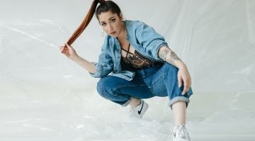 Hip Hop dance in denim jeans and jacket crouching on the floor against a white background